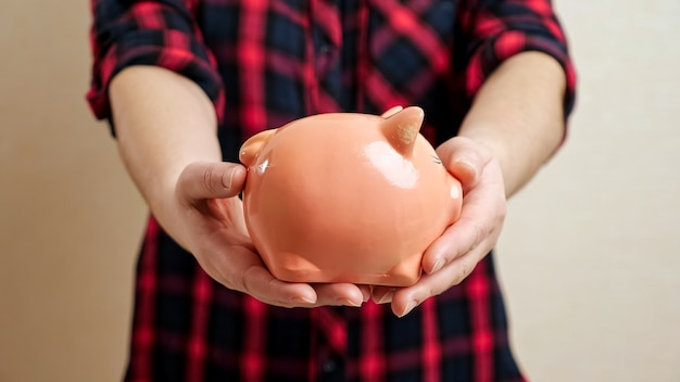 Woman extends slim arms holding small round piggy bank