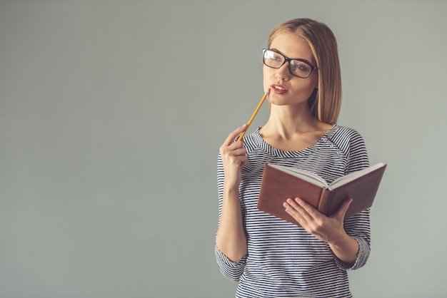 Woman in eyeglasses is holding a pencil and a notebook