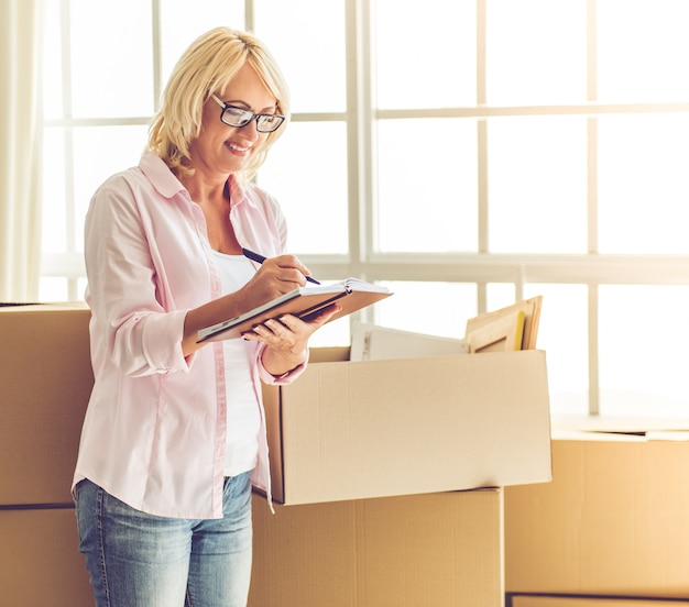 Woman in eyeglasses is packing her stuff into the boxes