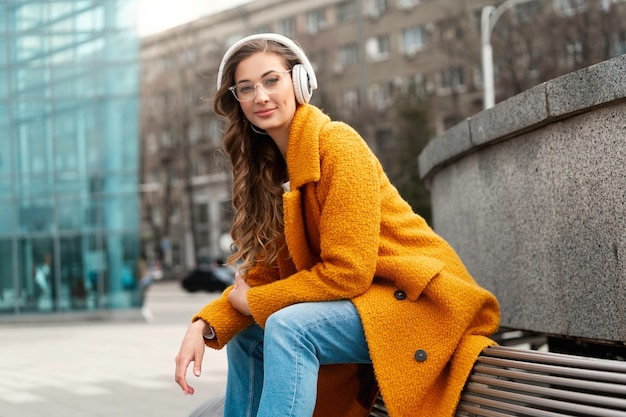 Женские очки слушать музыку наушники сидя на свежем воздухе скамейка на открытом воздухе одетая в стильное желтое пальто улыбка кавказская женщина 30 лет наслаждайтесь подкастами или аудиокнигами на улице