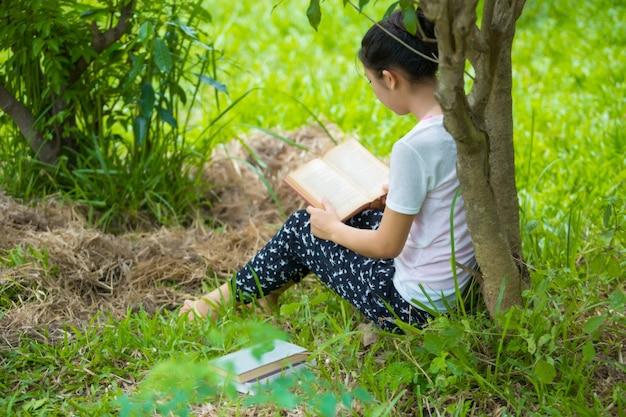Woman in eyeglasses reading book in park