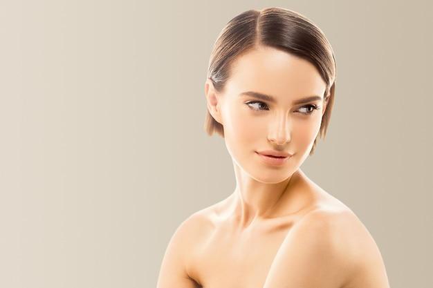 健康な肌に触れる女性の顔の美しさ手ナチュラルメイク美しい女性ベージュの背景 Premium写真