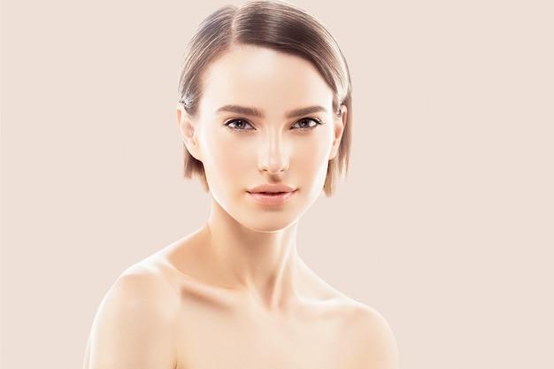 健康な肌に触れる女性の顔の美しさ手ナチュラルメイク美しい女性ベージュの背景