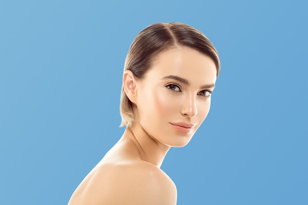 健康な肌に触れる女性の顔の美しさの手ナチュラルメイク美しい女性の青い背景