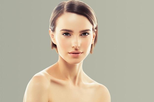 健康な肌に触れる女性の顔の美しさ手ナチュラルメイク美しい女性灰色の背景