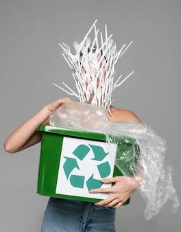Volto di donna ricoperto di forchette di plastica bianca mentre si tiene un cestino