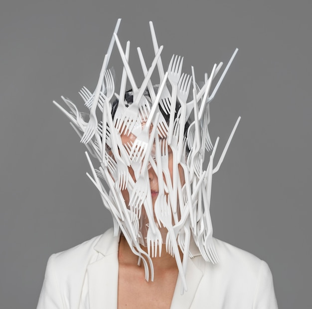 Woman face being covered in white plastic tableware