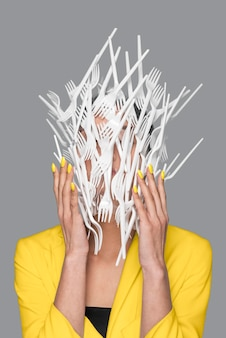 woman face covered in plastic tableware standing next to a ultimate gray wall