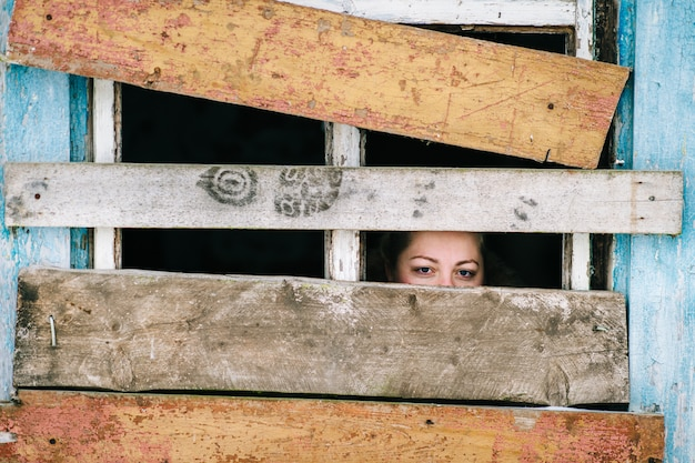 Woman face looking through old wooden window.