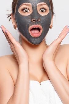 여자 얼굴 마스크입니다. 얼굴 피부에서 화장품 블랙 필링 마스크를 제거하는 아름 다운 여자의 초상화. 자연 메이크업과 얼굴에 화장품 껍질 마스크와 매력적인 젊은 여자의 근접 촬영. 높은 해상도