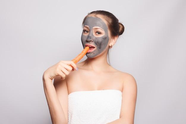 Маска для лица женщины. портрет красивой девушки, снимая косметическую черную пилинг-маску с кожи лица. макрофотография привлекательной молодой женщины с естественным макияжем и косметической пилинг-маской на лице. высокое разрешение