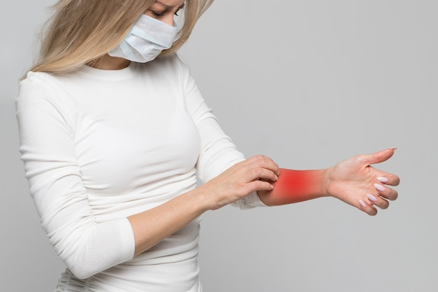 Woman in face mask scratching arm colored in red isolated