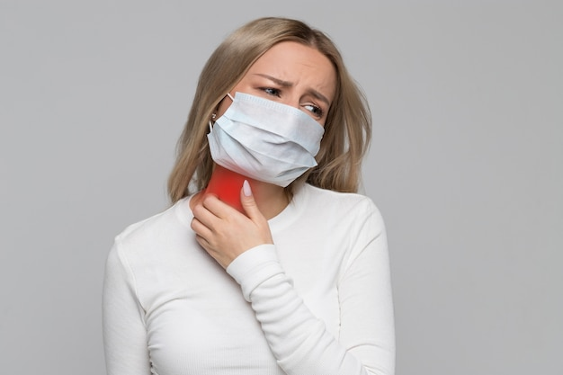 Woman in face mask scratching her neck