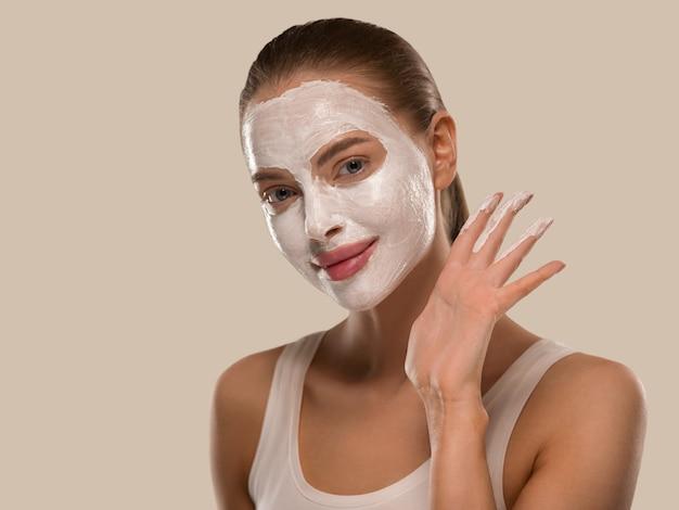 Мыло для мытья лица маски женщины заделывают чистую кожу. цвет фона коричневый