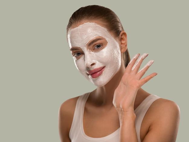 Мыло для мытья лица маски женщины заделывают чистую кожу. цвет фона зеленый