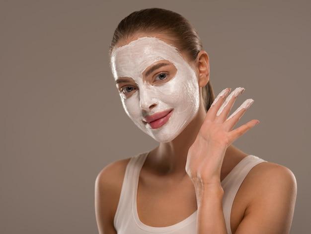 Мыло для мытья лица маски женщины заделывают чистую кожу. цвет фона
