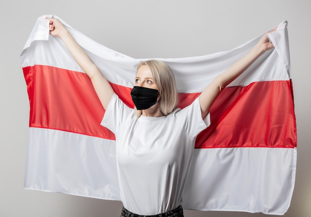 Woman in face mask with former national belarus flag on white wall