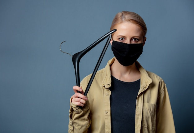 Woman in face mask with hanger, of female protest in poland