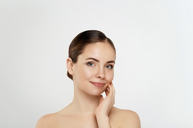 여자 얼굴 피부 관리. 그녀의 부드럽고 깨끗한 피부를 만지는 완벽한 전문 메이크업으로 아름다운 섹시한 여자.