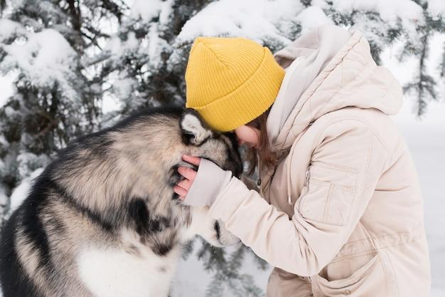 冬の森でアラスカン・マラミュートと対面する女性。犬。閉じる。