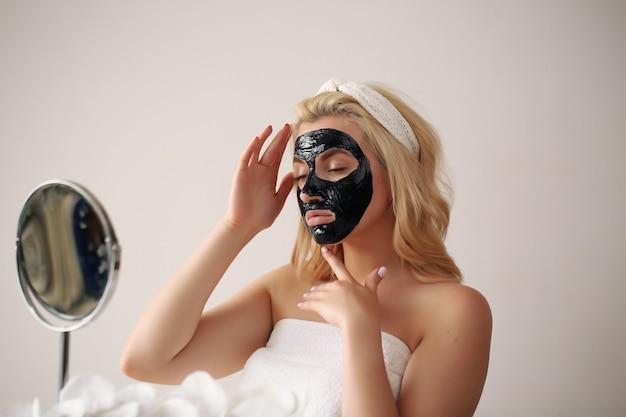 肌に黒いピーリングマスクを付けた女性の顔。顔に化粧マスクを適用します。
