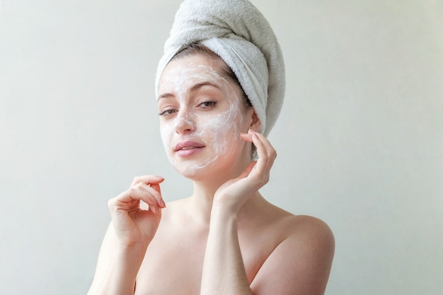 Woman face with cream or nourishing mask.