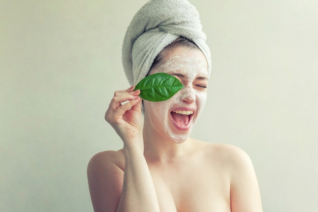 Woman face with green leaf and cream or nourishing mask