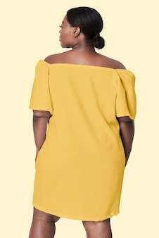 後ろ向きの黄色いドレスプラスサイズのアパレルファッションに直面している女性