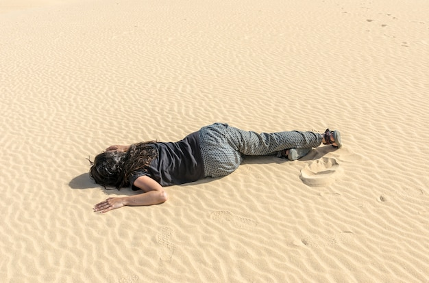 Woman fainted in the middle of the desert sand. she is dehydrated and lost.