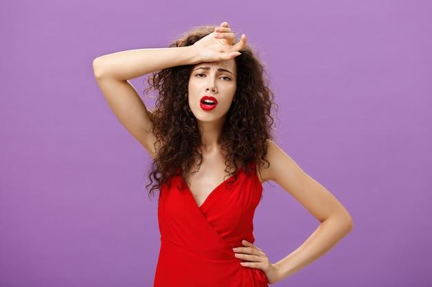 助けを求めている憂鬱で不幸な気持ちを表現する赤いスタイリッシュなドレスを着て、紫色の背景の上に立っている額の汗をかき消し、疲れ果てている女性の失神。コピースペース