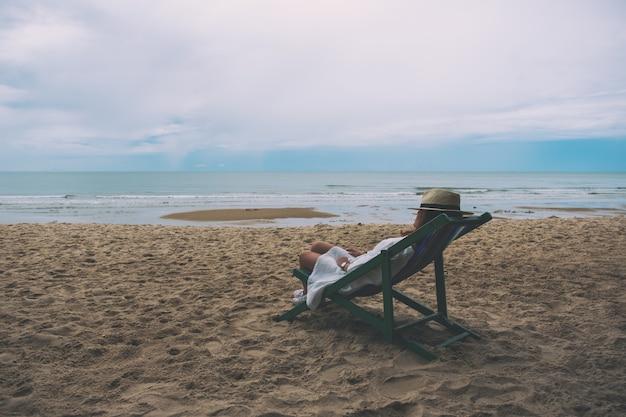 A woman fall asleep and lying down on a beach chair alone