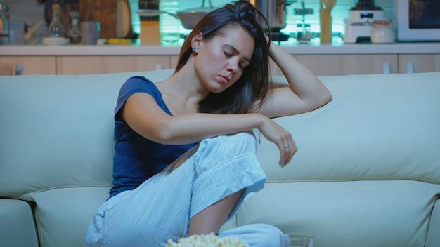 Tv 앞 소파에서 잠드는 여자. 피곤하고 지친 외로운 잠옷을 입은 외로운 잠옷이 거실의 아늑한 소파에 앉아 텔레비전 앞에서 잠을 자고 밤에 영화를 보면서 눈을 감습니다
