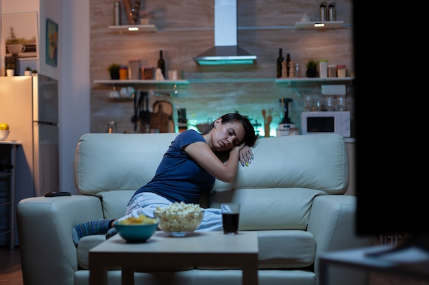 Woman falling asleep on sofa in front tv