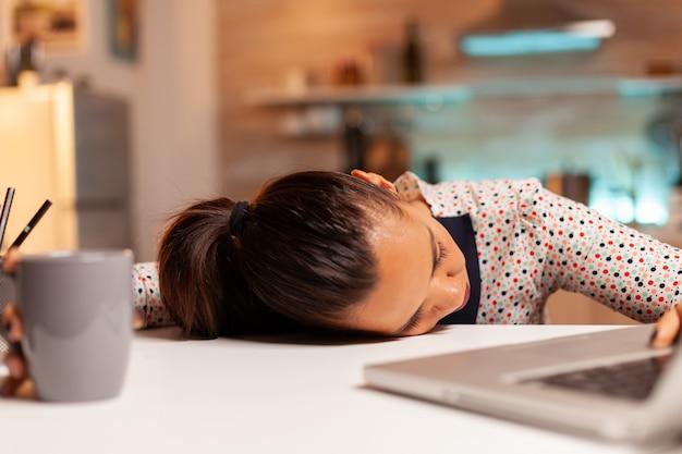 마감 시간에 집에서 일하는 동안 테이블에 머리를 대고 잠드는 여성. 자정에 현대 기술을 사용하는 직원은 작업, 비즈니스, 경력, 네트워크, 라이프스타일, 무선으로 초과 근무를 합니다.