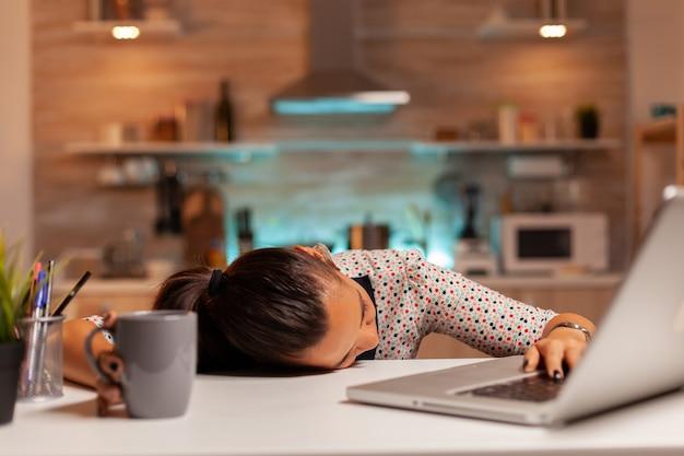 마감 시간에 집에서 일하는 동안 테이블에 머리로 잠들고있는 여자