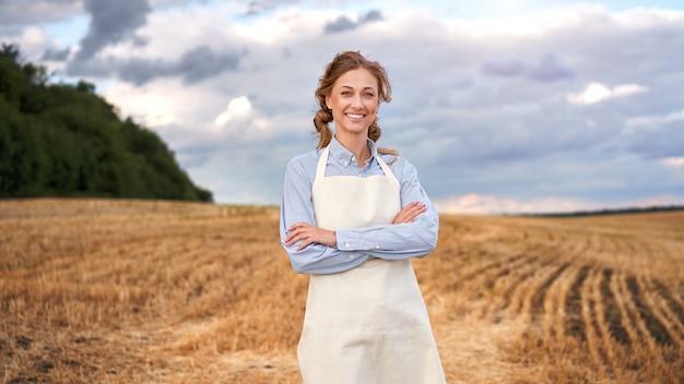 Woman farmer apron standing farmland smiling