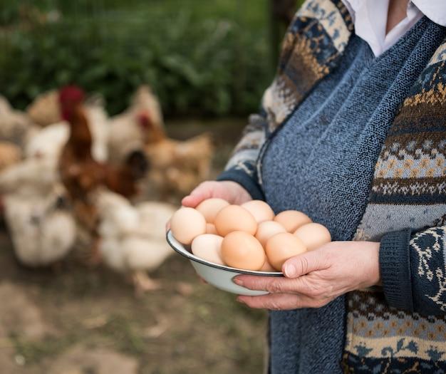 Женщина-фермер держит свежие органические яйца