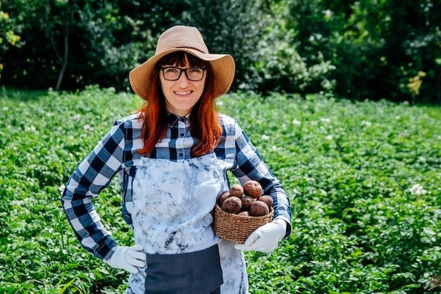女性農家は、野菜畑で麦わら帽子をかぶった籐のかごにじゃがいもを持っています