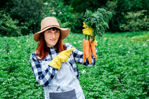 Woman farmer holds a bunch of carrots in a straw hat on background of a vegetable garden