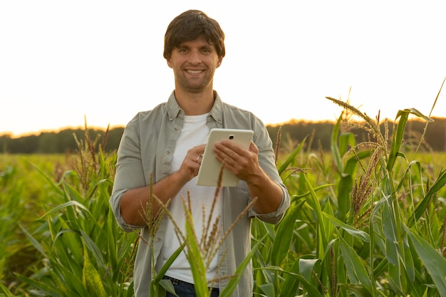 Женщина-фермер контролирует урожай кукурузы с помощью цифрового планшета