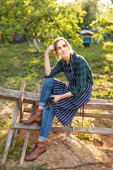 Woman farmer relaxing on a fence