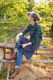 Женщина-фермер отдыхает на заборе
