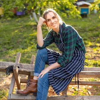 フェンスでリラックスした女性農家