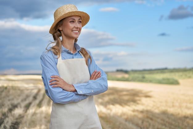 Woman farmer straw hat apron standing farmland smiling