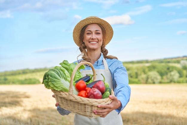 女性農家麦わら帽子エプロン立っている農地笑顔