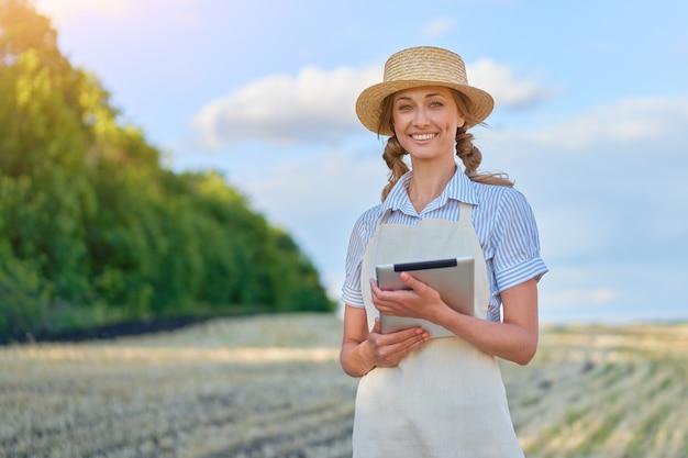 여성 농부 밀짚 모자 스마트 농업 서 농지 디지털 태블릿을 사용하여 웃고 여성 농업 경제학자 전문가 연구 모니터링 분석 데이터 농업