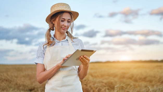 Woman farmer straw hat smart farming standing farmland smiling using digital tablet female agronomist specialist research monitoring analysis data agribusiness