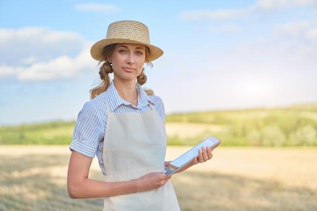 デジタルタブレットを使用して笑顔の女性農家麦わら帽子スマート農業立っている農地