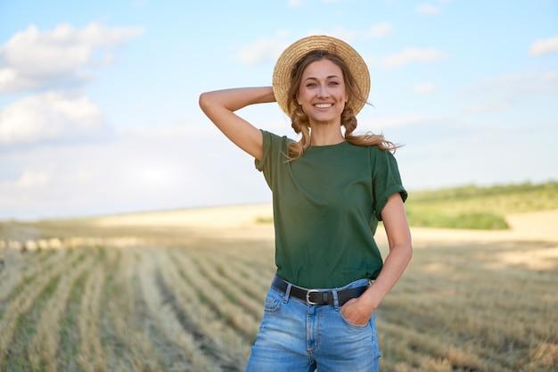 Woman farmer straw hat standing farmland smiling