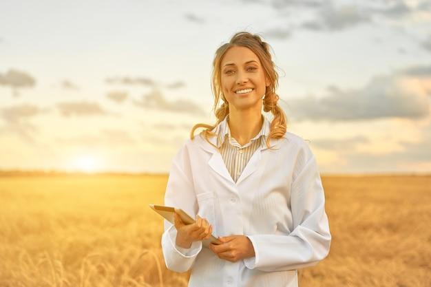 Женщина-фермер в белом халате, умное сельское хозяйство, стоя на сельскохозяйственных угодьях, улыбается с помощью цифрового планшета